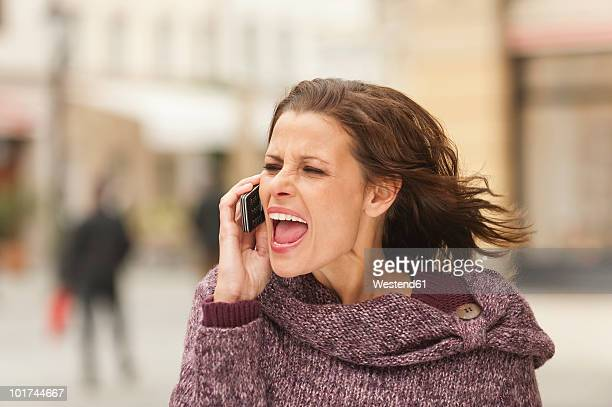 Germany, Bavaria, Munich, Woman using mobile phone, screaming, close-up