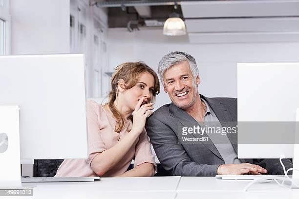 Germany, Bavaria, Munich, Woman whispering in man's ear in office