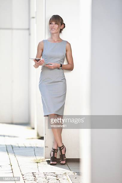 Germany, Bavaria, Munich, Young businesswoman with digital tablet leaning on wall