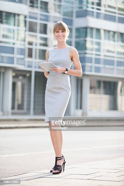 germany, bavaria, munich, young businesswoman with digital tablet on pavement - fringe dress stock pictures, royalty-free photos & images