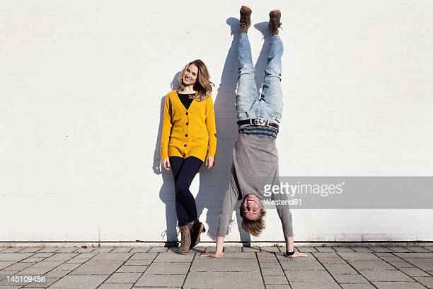 germany, bavaria, munich, young couple against wall, smiling - upside down stock pictures, royalty-free photos & images