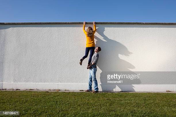 germany, bavaria, munich, young couple climbing wall - sollevare foto e immagini stock