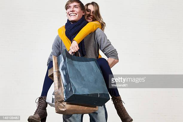 Germany, Bavaria, Munich, Young man carrying woman on his back while she holds shopping bags