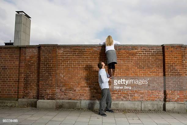Germany, Bavaria, Munich, Young man helping woman to climb wall