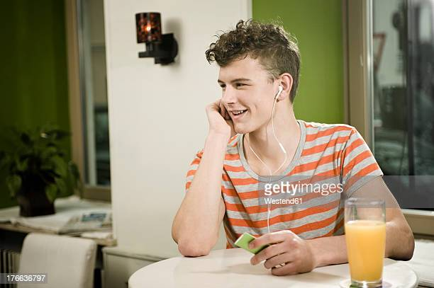 germany, bavaria, munich, young man listening music in cafe, smiling - mp3 juices stock photos and pictures