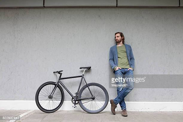 Germany, Bavaria, Munich, young man standing besides his racing cycle leaning on a wall
