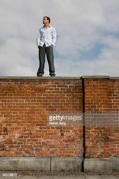 Germany, Bavaria, Munich, Young man standing on brick wall