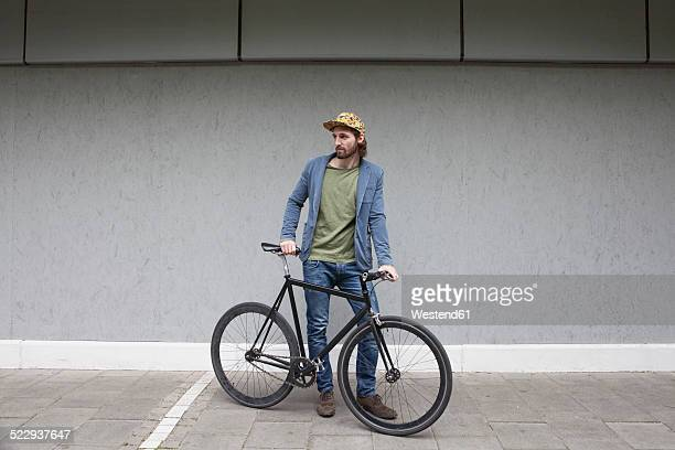 Germany, Bavaria, Munich, young man wearing basecap standing in front of a wall with his racing cycle