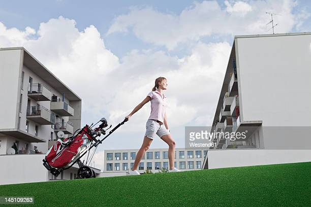 Germany, Bavaria, Munich, Young woman carrying golf cart