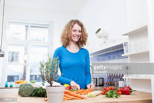 Germany, Bavaria, Munich, Young woman chopping vegetables in kitchen, smiling, portrait