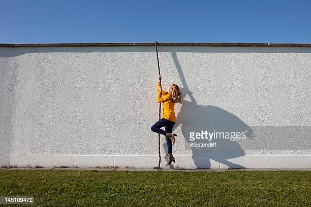 Germany, Bavaria, Munich, Young woman climbing wall with rope