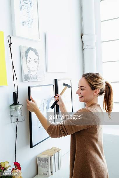 germany, bavaria, munich, young woman holding picture frame in front of wall - hausdekor stock-fotos und bilder