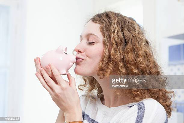 Germany, Bavaria, Munich, Young woman kissing piggy bank, smiling