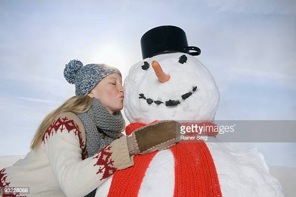 Germany, Bavaria, Munich, Woman kissing snowman, side view