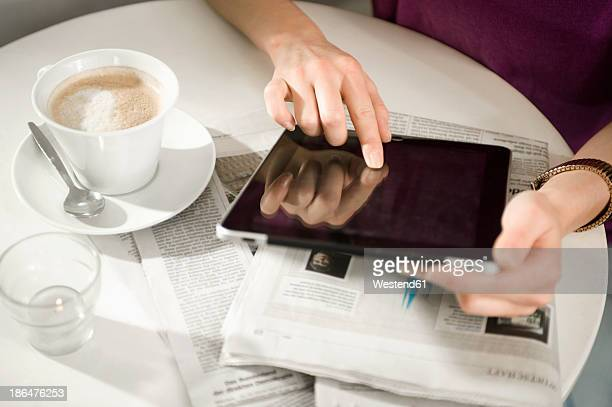 Germany, Bavaria, Munich, Young woman sitting at table in cafe, using digital tablet