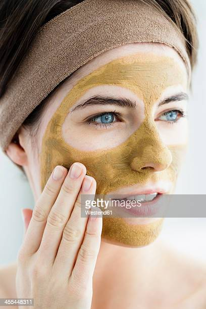 Germany, Bavaria, Munich, Young woman with clay mask, close up