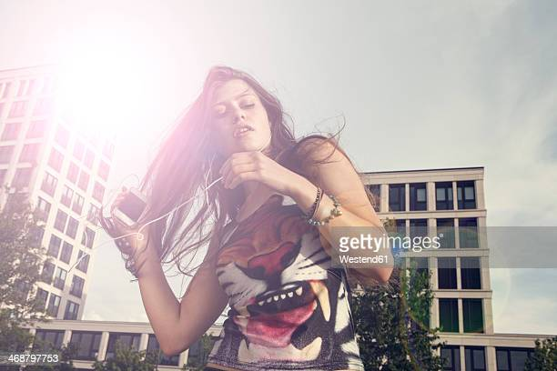 Germany, Bavaria, Munich, Young woman with smartphone and earphones outdoors