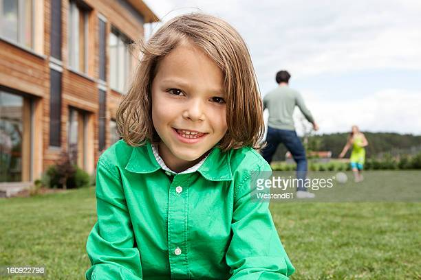 Germany, Bavaria, Nuremberg, Boy smiling, portrait, father and daughter playing in background