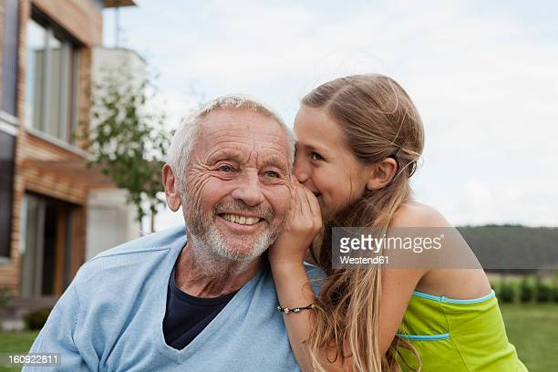 Germany, Bavaria, Nuremberg, Granddaughter whispering in grandfathers ear