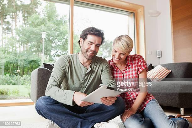 Germany, Bavaria, Nuremberg, Mature couple using digital tablet in living room