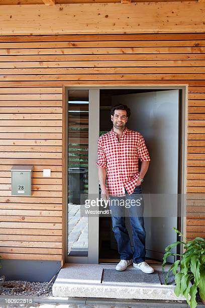 Germany, Bavaria, Nuremberg, Mature man standing at front door of house