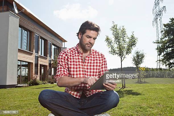 Germany, Bavaria, Nuremberg, Mature man using digital tablet in garden