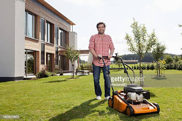 germany, bavaria, nuremberg, mature man with lawn mower in garden - lawn mower stock pictures, royalty-free photos & images