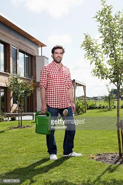 germany, bavaria, nuremberg, mature man with watering can in garden - einzelner mann über 40 stock-fotos und bilder