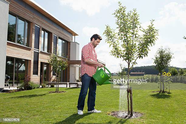 Germany, Bavaria, Nuremberg, Mature man with watering can in garden