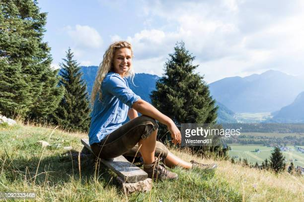 germany, bavaria, oberammergau, portrait of smiling young woman sitting on bench on mountain meadow - bavaria stock pictures, royalty-free photos & images