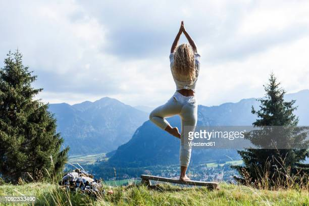 germany, bavaria, oberammergau, young woman doing yoga on bench on mountain meadow - gleichgewicht stock-fotos und bilder