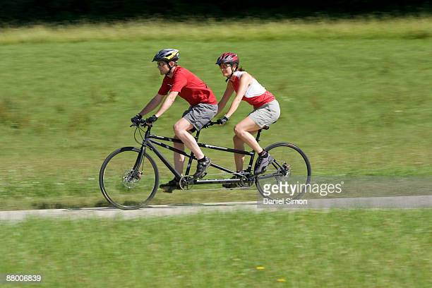 germany, bavaria, oberland, couple mountain biking on tandem - tandem bicycle stock pictures, royalty-free photos & images