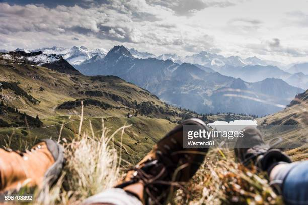 Germany, Bavaria, Oberstdorf, feet of two hikers resting in alpine scenery