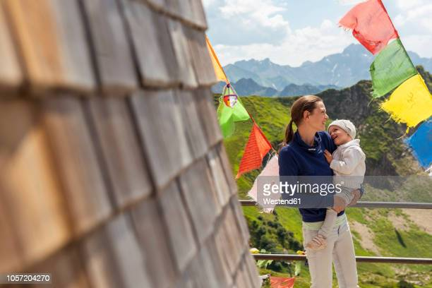 germany, bavaria, oberstdorf, happy mother carrying little daughter on a mountain hut surrounded by pennants - oberstdorf stock pictures, royalty-free photos & images