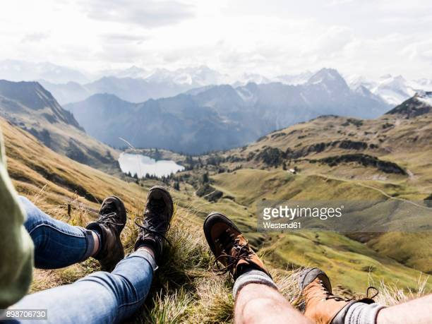 germany, bavaria, oberstdorf, legs of two hikers resting in alpine scenery - ブーツ ストックフォトと画像