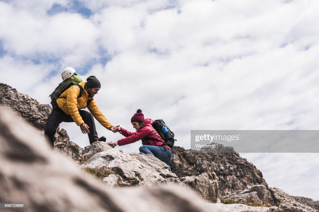 Germany, Bavaria, Oberstdorf, man helping woman climbing up rock : Stock Photo