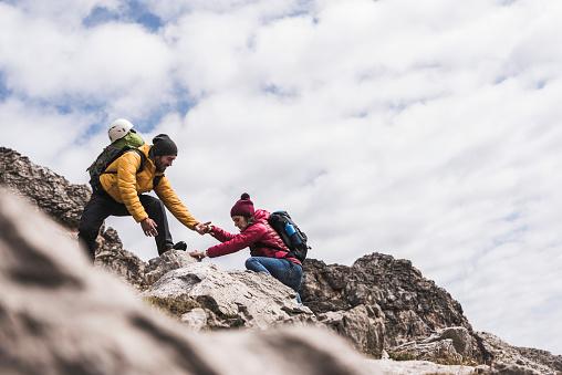 Germany, Bavaria, Oberstdorf, man helping woman climbing up rock - gettyimageskorea