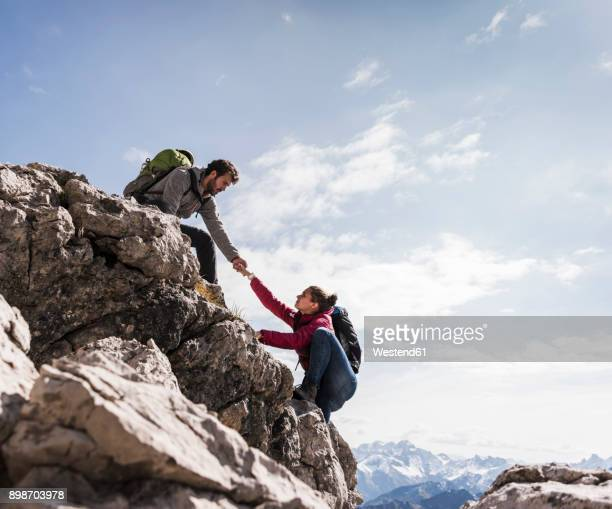 germany, bavaria, oberstdorf, man helping woman climbing up rock - oberstdorf stock pictures, royalty-free photos & images