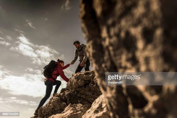 germany, bavaria, oberstdorf, man helping woman climbing up rock - herausforderung stock-fotos und bilder