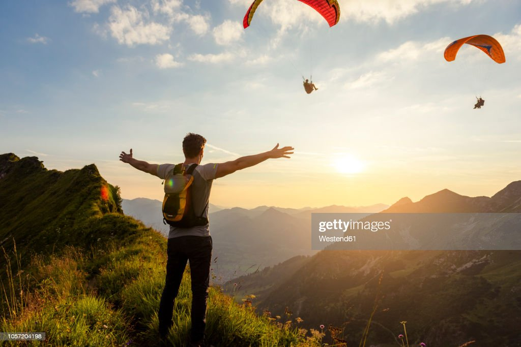 Germany, Bavaria, Oberstdorf, man on a hike in the mountains at sunset with paraglider in background : Stock-Foto