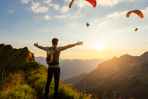 Germany, Bavaria, Oberstdorf, man on a hike in the mountains at sunset with paraglider in background - gettyimageskorea