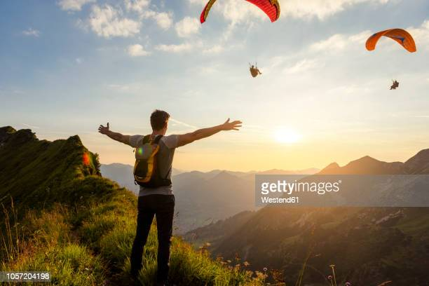germany, bavaria, oberstdorf, man on a hike in the mountains at sunset with paraglider in background - lebensziel stock-fotos und bilder