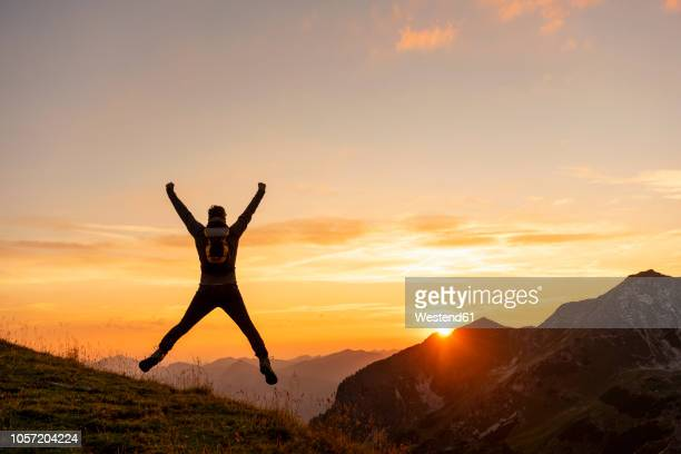 germany, bavaria, oberstdorf, man on a hike in the mountains jumping at sunset - ganar fotografías e imágenes de stock