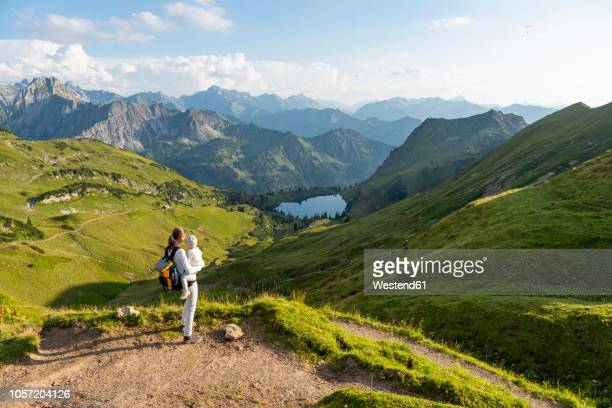 germany, bavaria, oberstdorf, mother and little daughter on a hike in the mountains looking at view - bavaria stock photos and pictures