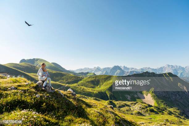 germany, bavaria, oberstdorf, mother and little daughter on a hike in the mountains having a break looking at view - bavaria stock photos and pictures