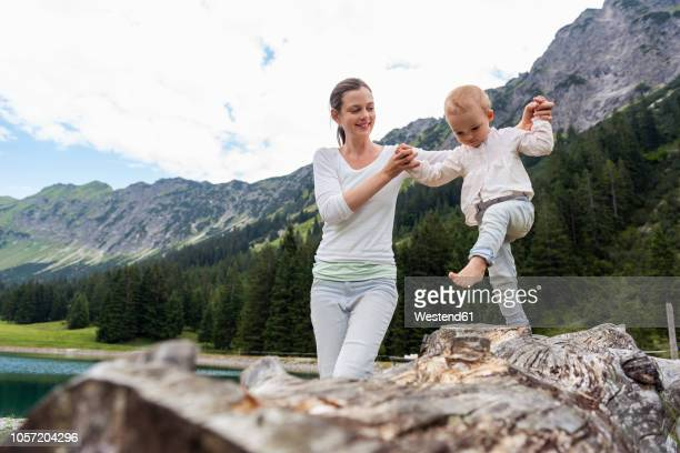 germany, bavaria, oberstdorf, mother helping little daughter balancing on a log - oberstdorf stock pictures, royalty-free photos & images