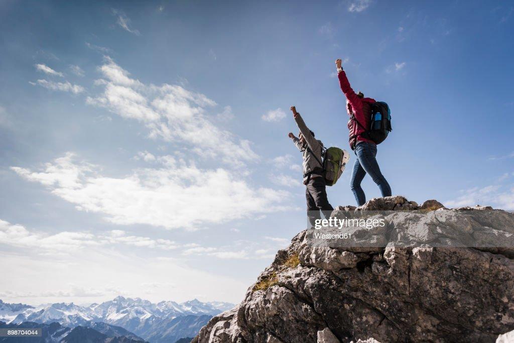Germany, Bavaria, Oberstdorf, two hikers cheering on rock in alpine scenery : Stock-Foto