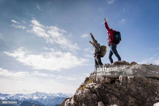 germany, bavaria, oberstdorf, two hikers cheering on rock in alpine scenery - mountain peak stock pictures, royalty-free photos & images