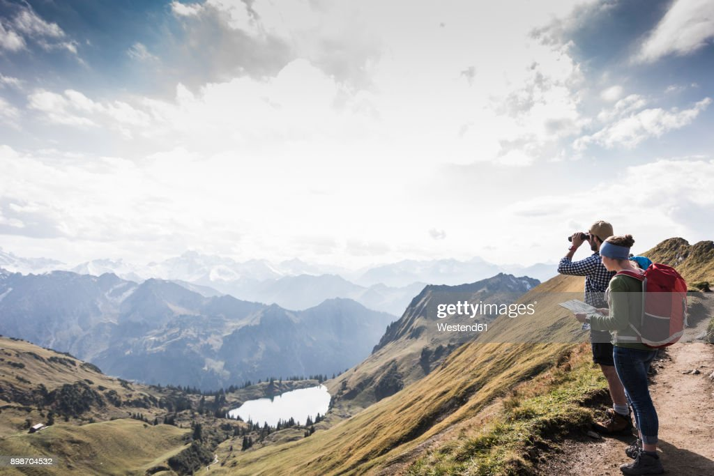 Germany, Bavaria, Oberstdorf, two hikers with map and binoculars in alpine scenery : Stock-Foto