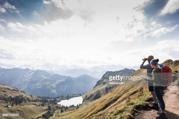 germany, bavaria, oberstdorf, two hikers with map and binoculars in alpine scenery - rucksacktourist stock-fotos und bilder